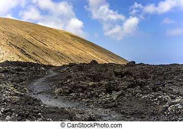 Road to vulcano Caldera Blanca, a volcano on Lanzarote, in...