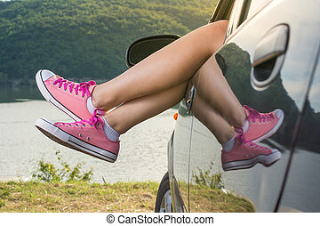 Legs out of the car window by the lake