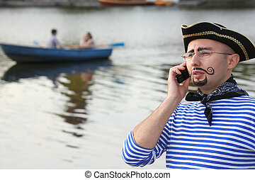 man in pirate suit is talking by the phone. boat in out of focus