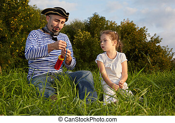 dad in pirate suit and daughter is sitting on grass. dad get ready to inflate air-balloon