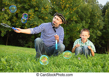 man with drawed beard and whiskers is blowing soap bubbles. his son is looking on little soap bubble.