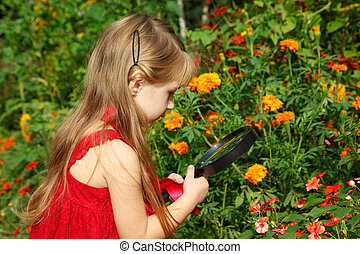 Little girl in red dress considers flower through magnifying...