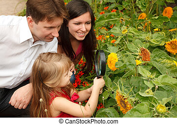 Little girl in red dress considers flower together with...