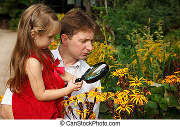 Little girl in red dress with father, considers plants...