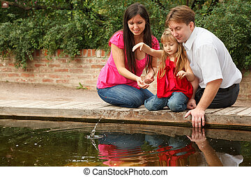 Little girl in red dress throws stones in water together with parents.