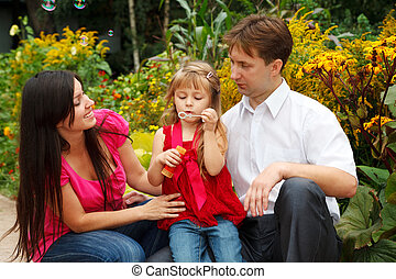 Little girl in red dress blows soap bubbles in summer garden together with parents.