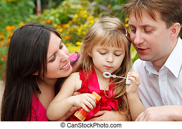 Parents observe as their daughter in red dress blows soap bubbles in summer garden. Close up.