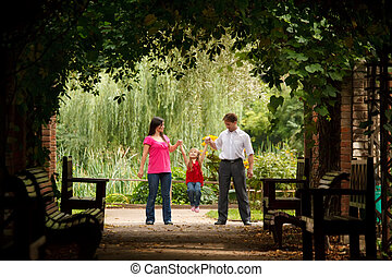 Little girl in red dress with father and mother in park in plant tunnel. Girl plays being shaken on hands of parents. Horizontal format