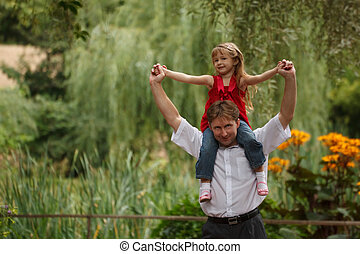 Portrait of man with a daughter in summer garden. Girl sits at father on shoulders.