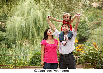 Little girl in red dress together with parents in summer garden. Girl sits on shoulders at father.