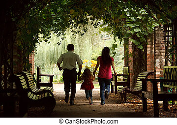 Parents together with daughter escape on tunnel from ivy in summer garden.