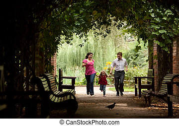 Parents together with daughter run on tunnel from ivy in summer garden.