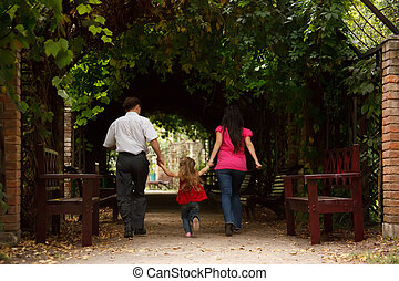 Parents together with daughter enter into tunnel from an ivy...