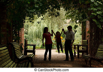 Parents and little girl in summer garden in plant tunnel. Girl plays being shaken on hands of parents.