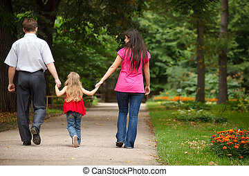 Parents together with daughter walk on summer garden. Leave...