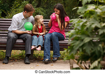 Parents together with daughter on bench in park in...
