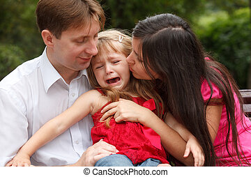 Parents calm crying girl on walk in summer garden. Girl sits...