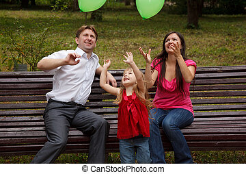 Parents together with daughter on bench in park in afternoon. Play with green balloon.