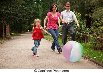 Little girl in jeans and red dress plays with big inflatable ball in park together with parents.