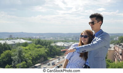 Young couple man and woman stand next to each other, above town, in sunglasses and discuss a beautiful panorama.