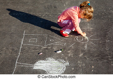 girl sits on concrete asphalt square road. girl draws painting line a chalk on asphalt. chld drawings paintings on asphalt concrete