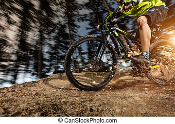 Low angle view of mountain biker riding on trail - Low angle...