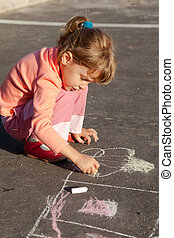 girl sits on concrete asphalt square road. girl draws painting line house a chalk on asphalt. chld drawings paintings on asphalt concrete. side view