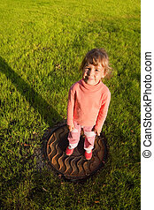 girl is standing on hatch in grass. smiling little girl view from above. water drain rusty hatch on grass field