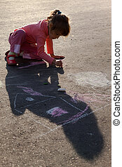 girl sits on concrete asphalt square road. girl draws painting line sun house tree a chalk on asphalt. chld drawings paintings on asphalt concrete. front side view