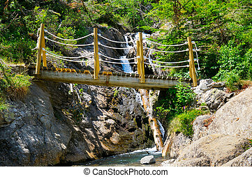 bridge over a mountain river and stony bank