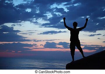 Silhouette guy lifted hands upwards on breakwater in evening near sea