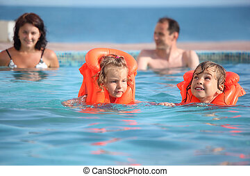 two little girls bathing in life jackets with parents in pool on a resort