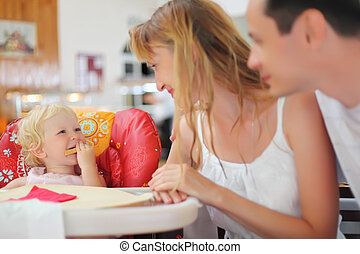 Happy family with blond little girl eating bread