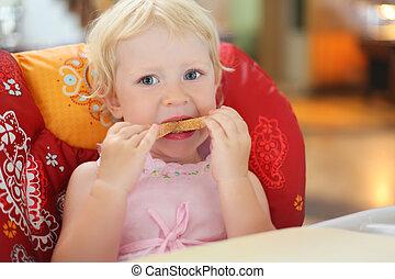 pretty blond little girl eats bread, sitting in an armchair