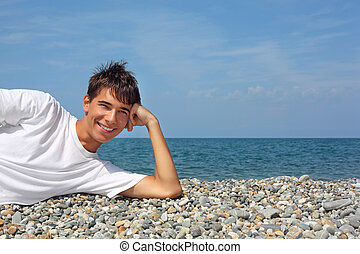 teenager boy in white T-shirt lying on stony seacoast