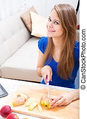 Cutting apple while getting online information about...