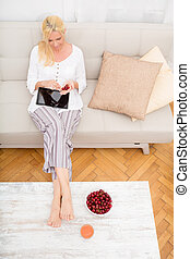 Woman with Tablet pc on the sofa - A mature woman in Pyjamas...