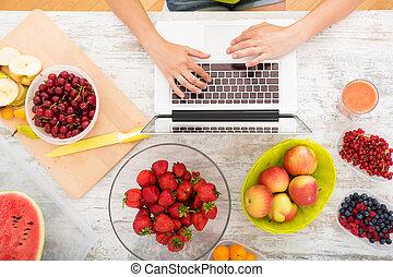 Researching Fruits - A beautiful mature woman using a Laptop...