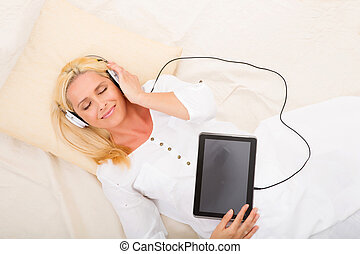 Woman with headphones and tablet in bed - A middle aged...