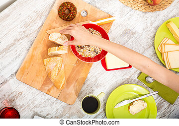 Young woman preparing a european breakfast - A young adult...