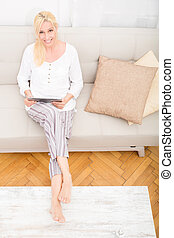 Woman with tablet on the sofa - A mature woman in pyjamas...