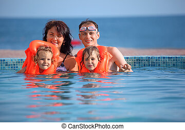 two little girls bathing in lifejackets with parents in pool...