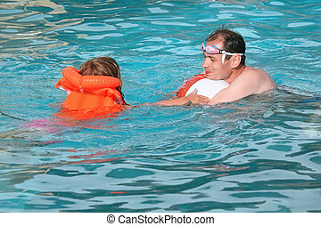 young man and little girl in lifejacket bathing in pool on...