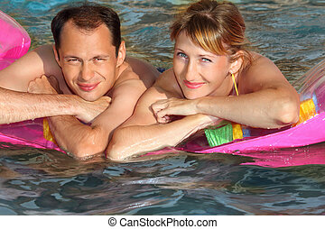young man and nice women lying on an inflatable mattress in pool, top view