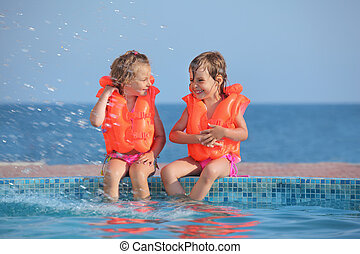 two little girls in lifejackets sitting on ledge pool on...