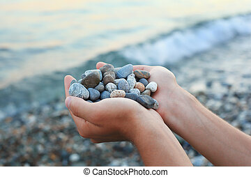 Handful of stones in hands, Against stones and sea