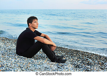 sitting teenager boy on stone seacoast, Looking afar