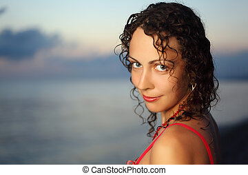 Curly beautiful young woman near sea in evening, Steadfastly looking