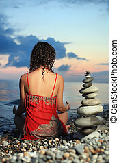 beautiful woman in red sundress meditating near to pyramid...