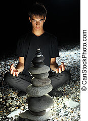 teenager boy meditating near pyramid from pebble on stony...